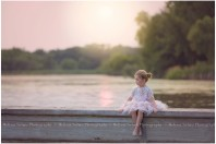 Little Ballerina sitting on dock at sunset